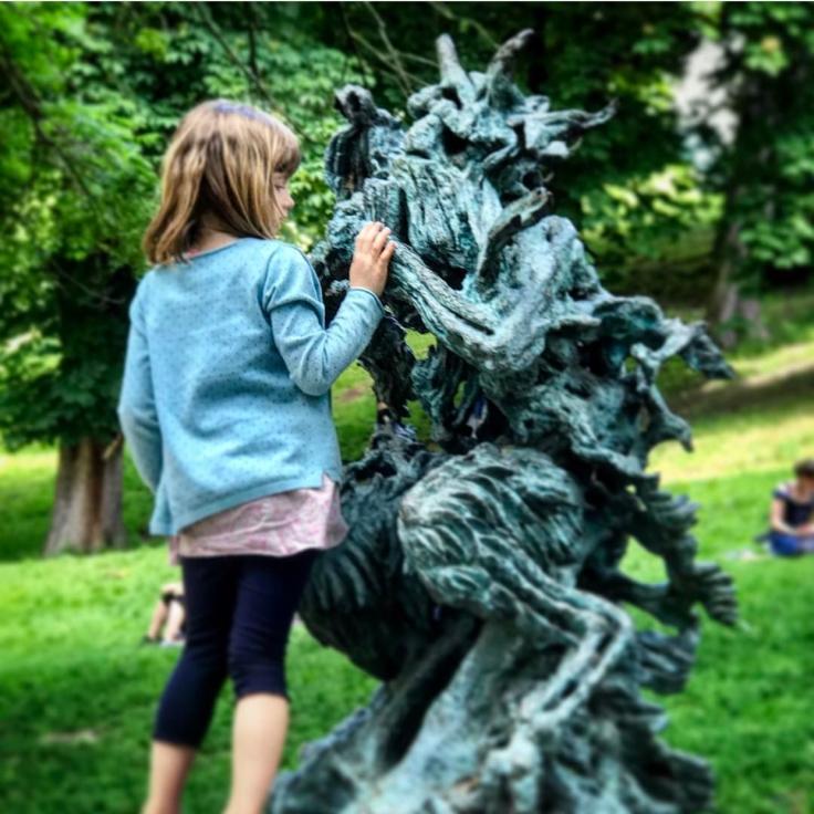 Una bambina accanto alla statua di Pan, dio della natura e dei boschi.